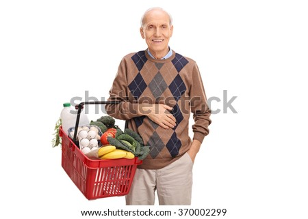 Cheerful senior gentleman holding a shopping basket full of groceries isolated on white background - stock photo