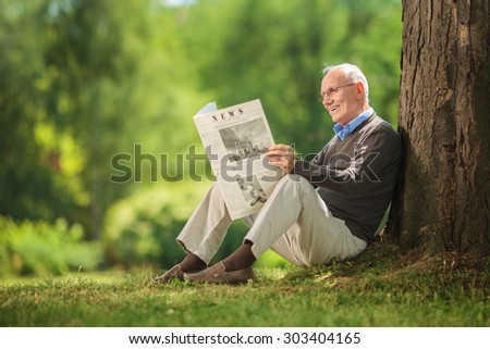 Cheerful senior gentleman reading a newspaper in park and leaning against a tree seated on the ground on beautiful summer day - stock photo