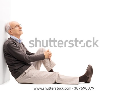Cheerful senior gentleman sitting on the floor and leaning against a wall isolated on white background - stock photo