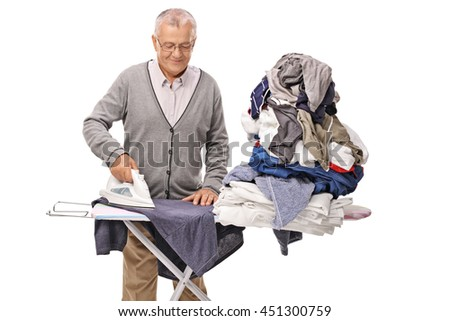 Cheerful senior man ironing a pile of clothes on an ironing board isolated on white background - stock photo