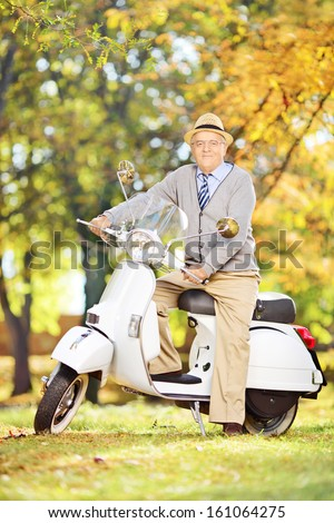 Cheerful senior man on a scooter posing and looking at camera in a park