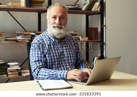 cheerful senior man with laptop in office looking at camera and smiling - stock photo