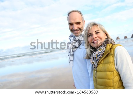 Cheerful senior people walking on the beach - stock photo