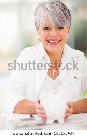 cheerful senior woman holding piggybank  - stock photo