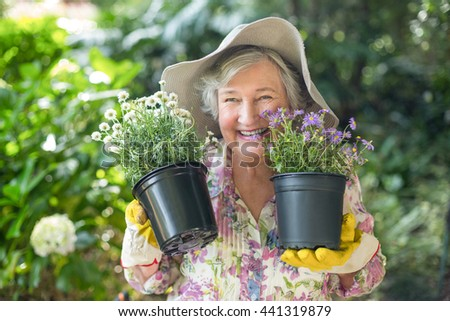 Cheerful senior woman holding potted plants in garden - stock photo