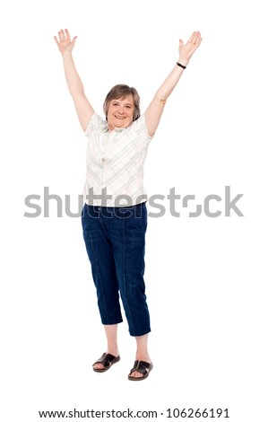 Cheerful senior woman lifting her arms up filled with joy - stock photo
