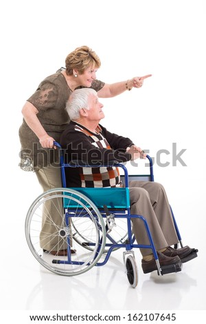 cheerful senior woman pointing while her disabled husband on wheel chair - stock photo