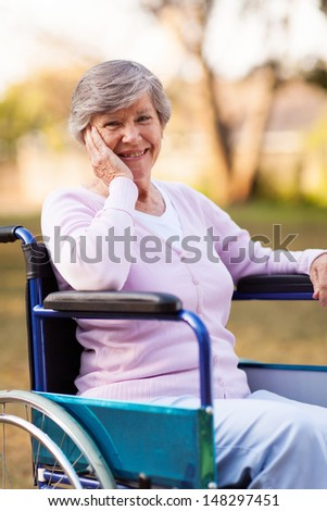 cheerful senior woman sitting on a wheelchair outdoors - stock photo