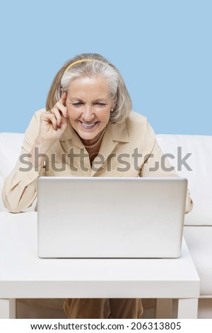 Cheerful senior woman using laptop for video calling - stock photo