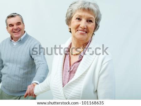 Cheerful seniors holding hands romantically - stock photo