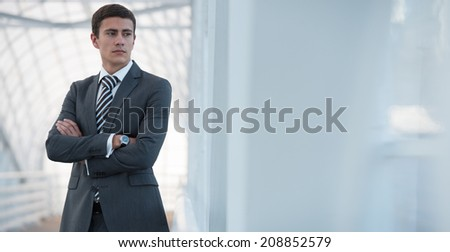 Cheerful serious young businessman standing in urban surrounding with arms crossed - stock photo