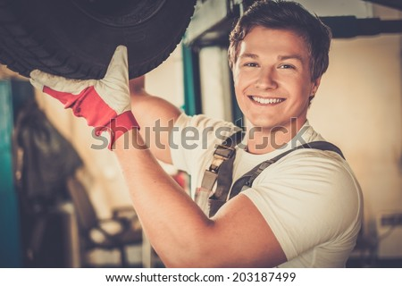 Cheerful serviceman checking suspension in a car workshop  - stock photo