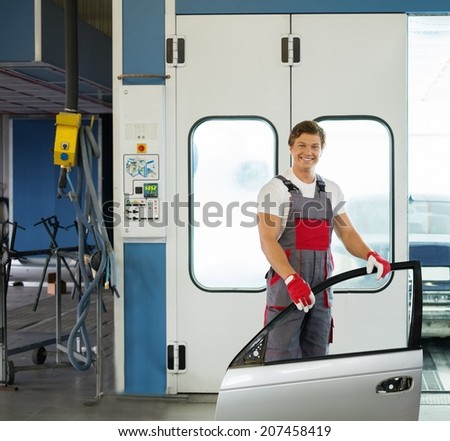 Cheerful serviceman with car door near paint booth in a car body workshop - stock photo