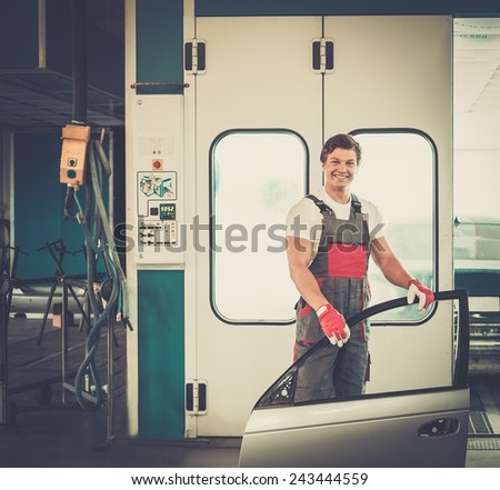 Cheerful serviceman with car door near paint booth in a car body workshop