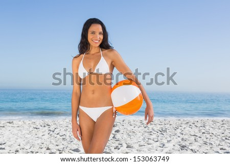 Cheerful sexy brunette in white bikini with beach ball on the beach