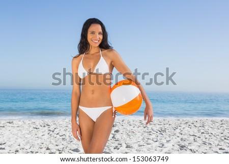 Cheerful sexy brunette in white bikini with beach ball on the beach - stock photo