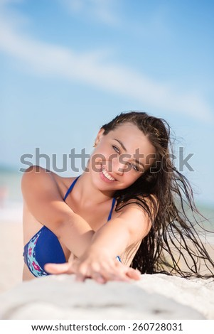 Cheerful sexy brunette posing on the beach - stock photo