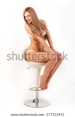 Cheerful sexy model in a chair - stock photo