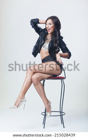 Cheerful sexy woman posing on a chair - stock photo