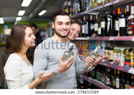 Cheerful shoppers with bottles of vodka at supermarket. Focus on guy - stock photo