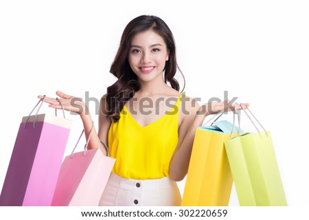 Cheerful shopping woman of Asian holding bags. Shopping woman happy smiling holding shopping bags isolated on white background. Lovely fresh young Asian female model. - stock photo