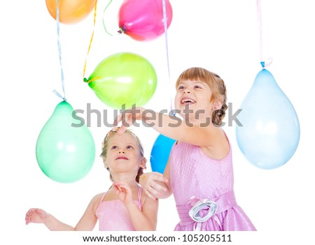 Cheerful siblings playing with balloons - stock photo