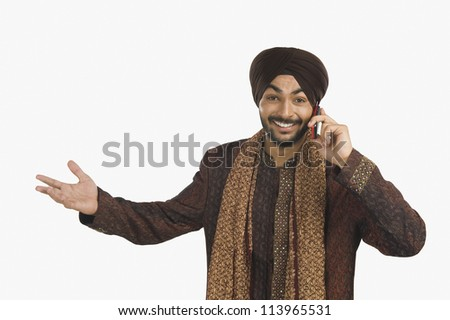 Cheerful Sikh man talking on a mobile phone and gesturing - stock photo