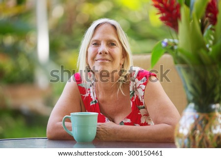 Cheerful single adult female with grin outdoors - stock photo