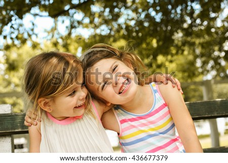 Cheerful sisters sitting on bench and enjoying.   - stock photo
