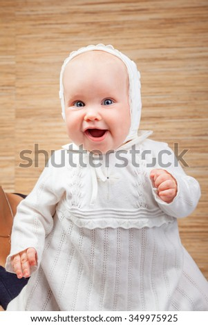 Cheerful six month baby girl wearing white christening clothes - stock photo