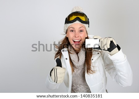 Cheerful skier woman showing ski pass - stock photo