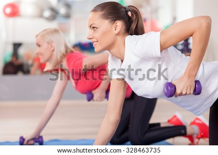 Cheerful slim girls are exercising in fitness center. They are kneeling and holding dumbbells. The ladies are smiling and looking forward confidently - stock photo