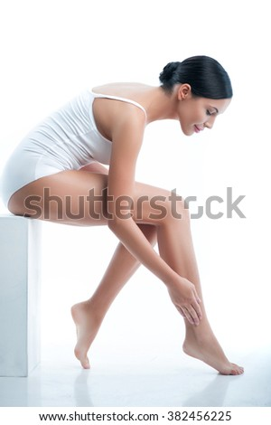 Cheerful slim woman is caring of her skin - stock photo