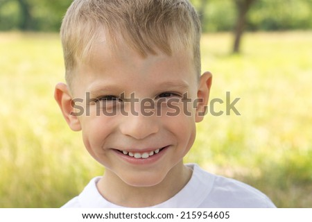 Cheerful small boy at summer park smiling looking straight into camera. Caucasian child at outdoor - stock photo
