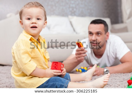 Cheerful small boy is sitting on carpet and holding a toy. He is looking at the camera and smiling. He parent is lying near him and giving him a plaything with joy - stock photo