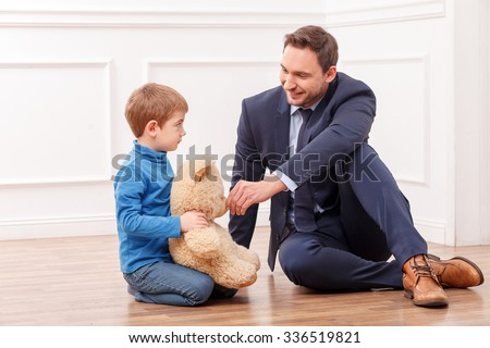 Cheerful small child is sitting on flooring near his father. He is holding a Teddy bear and looking at the busy man with abuse. The man is trying to calm down his son and smiling - stock photo