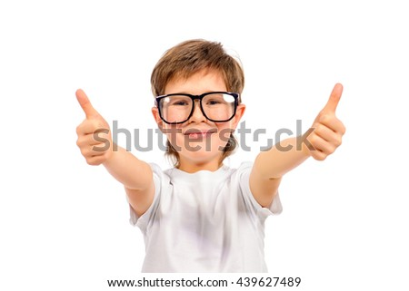 Cheerful smart boy in big glasses looking at the camera and showing thumb. Education. Studio shot. Isolated over white. - stock photo