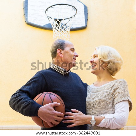 Cheerful smiling active senior spouses playing basketball in patio - stock photo