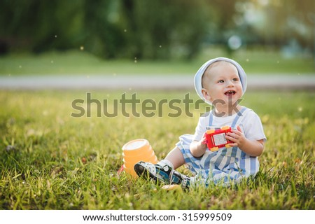 cheerful smiling baby boy is playing in the park - stock photo