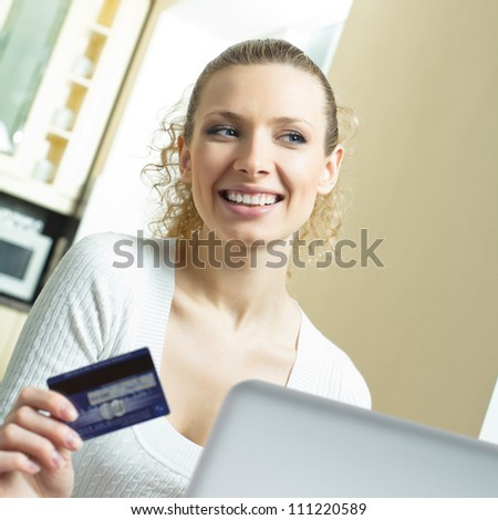 Cheerful smiling blond woman paying by plastic card with laptop, indoors - stock photo