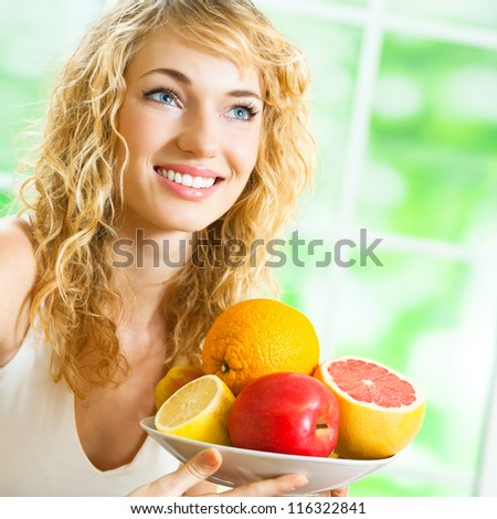 Cheerful smiling blond woman with fruits - stock photo
