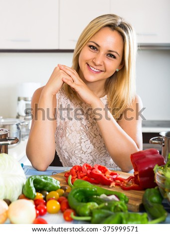 Cheerful smiling blonde girl preparing healthy meal with veggies at home