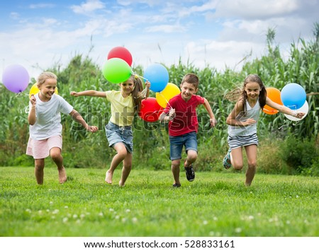 cheerful smiling boy and girls holding air balloons and running in summer park. Selective focus