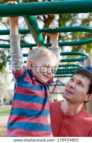cheerful smiling boy and his handsome young father having fun at the playground together - stock photo