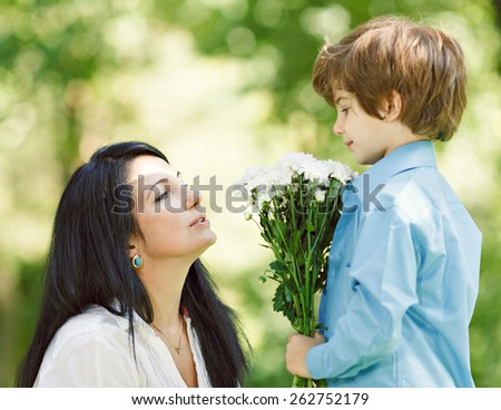 Cheerful smiling boy (child, kid) and woman with bouquet of  flowers playing on spring park. Mother`s day concept - stock photo