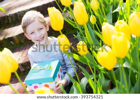cheerful smiling boy holding colorful present for mother's day or other celebration by the blooming tulips at park at spring time - stock photo