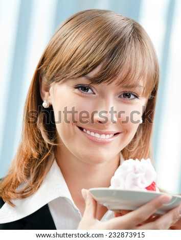 Cheerful smiling business woman with cake at office - stock photo
