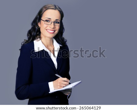 Cheerful smiling businesswoman in black suit with notepad or organizer, with blank copyspace area for text or slogan, over violet background