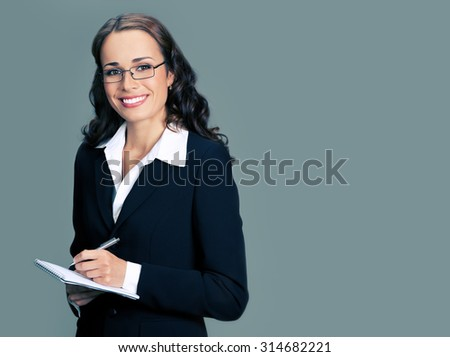 Cheerful smiling businesswoman in black suit with notepad or organizer, with blank copyspace area for slogan or text - stock photo