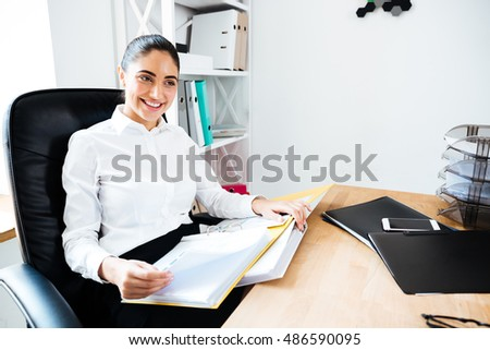 Cheerful smiling businesswoman reading documents while sitting at the office desk